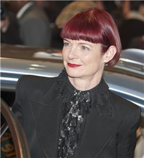 A red-haired woman is seen sporting a black outfit.