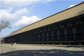 A very long wooden building with open veranda and slightly raised roof.