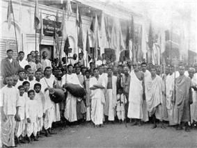 A group of India people with drums and flags in a semicircle