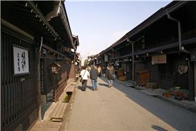 Small street lined by low two-storied wooden houses.