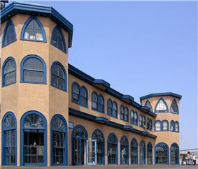 Exterior photograph of the Santa Monica Looff Hippodrome, a pink building with blue trim and large, arched glass doors and windows.