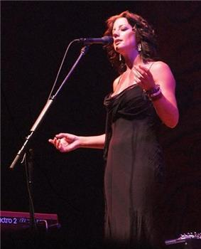 Woman wearing a black gown and singing in to a microphone.