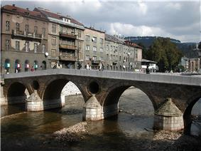 Latin bridge (prev. Princip bridge) in Sarajevo. Across the bridge is a street of several grayish houses not more than four stories high.