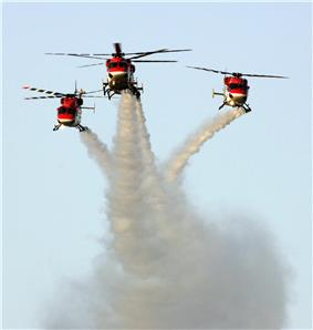 three helicopters flying in formation, making smoke trails in the sky