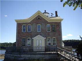 A brick building with yellow wooden trim and a pointed roof with a chimney and weather instruments on the roof. On the other side part of a lighthouse is visible. A wooden ramp leads up to a deck on its stone foundation surrounded by an iron fence.