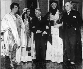 photopraph of Carl Nielsen in a suit linking arms with costumed members of the cast of Saul and David