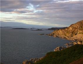 A sunlit rocky promontory at right and a calm, dark sea at left. Small dark islands pepper the waters in the distance