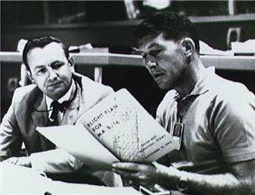 Two men seated at a desk, both reading from a large book the younger man is holding