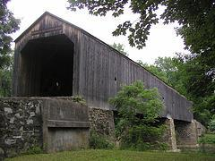 The front entrance and right side of an unpainted covered bridge supported by stone piers</center>