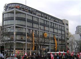 A seven-story, modern building, predominantly grey and white, with a cross-like symbol and large letters spelling