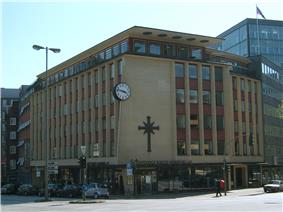 A 1950s or 1960s six-story building, predominantly made of yellow brick with red brick used around the windows. Other ornamentation include a large round black and white clock, a large black cross symbol, and