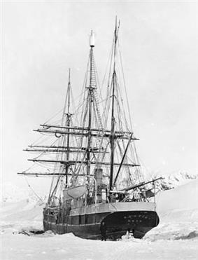 Rear view of a three-masted sailing ship with all sails furled, lying in an ice-covered sea.