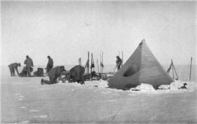 Six men are working with sleds and camping equipment, close to a pointed tent pitched on a snowy surface. Nearby, upright skis have been parked in the snow