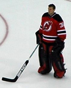 An ice hockey player standing, looking to the left of the camera. He is wearing a red and black uniform and is holding his hockey stick out in front.