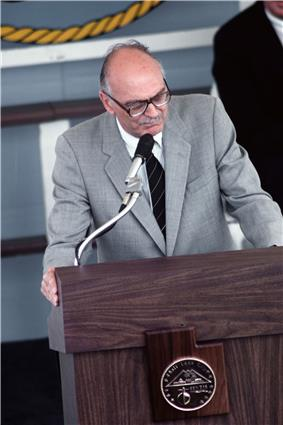 Late-twentieth-century man in a suit standing at a podium.