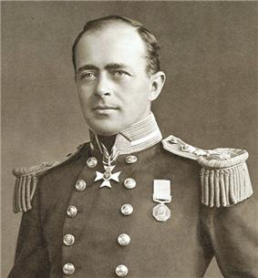 Man with receding hairline, looking left, wearing naval uniform with medals, polished buttons and heavy shoulder decorations