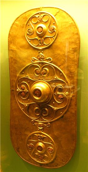 Golden shield dominated by three circular decorations. The larger central decoration has a large boss surrounded by a curlicue pattern. The smaller decorations above and below it are similar.