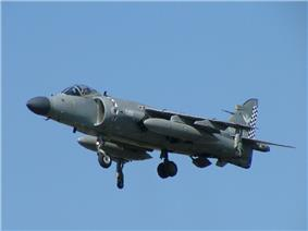 Grey jet aircraft with black radome hovering, undercarriage extended