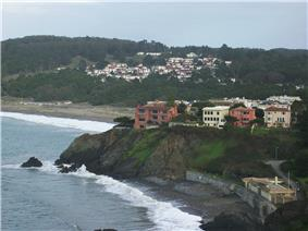 China Beach is seen in the foreground with the sea wall. Baker Beach can be seen in the distance