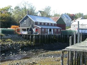 View of several wooden buildings at Seal Cove at low tide
