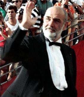 A man in his late fifties is waving his right hand. He is wearing a tuxedo and a black bow tie.