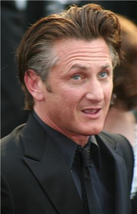 A picture of a man with wavy brown and grey hair is seen wearing a black suit, shirt, tie, and coat.