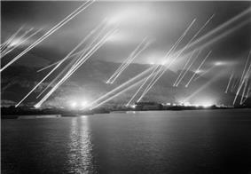 The Rock of Gibraltar, seen from the west, with at least 23 searchlights sending beams of light up into the night sky