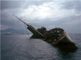 A half-sunken ship lies listing at 45 degrees