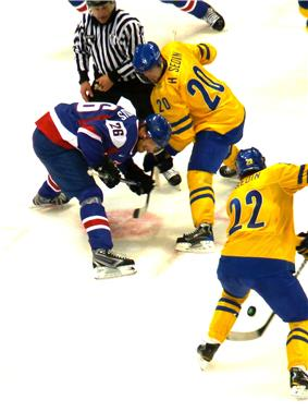 A faceoff during an ice hockey game. The player at the top left has directed the puck to his teammate next to him as his opponent, bent over, looks on.