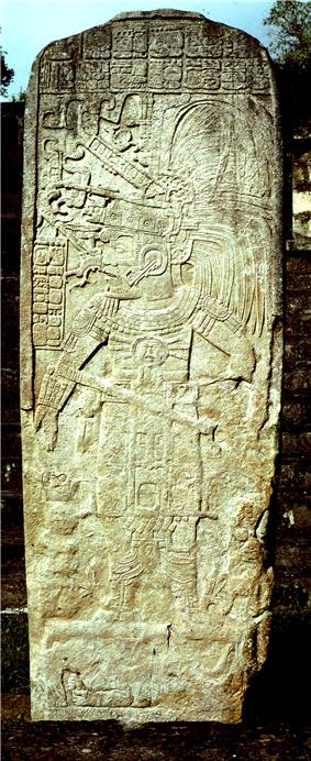 An upright stone shaft showing a figure looking to the left, holding a staff in one hand and wearing an elaborate feathered headdress. There are panels of hieroglyphs above and to the left of the figure.