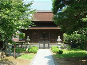 Front view of a wooden building with hip-and-gable roof and an enclosing pent roof.