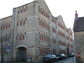 Corner of four-storey building with multiple matching arched windows