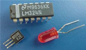 A small square plastic piece with three parallel wire protrusions on one side; a larger rectangular plastic chip with multiple plastic and metal pin-like legs; and a small red light globe with two long wires coming out of its base.