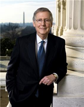 A man in his late sixties with graying hair and glasses leaning against a column and wearing black suit, white shirt, and blue tie