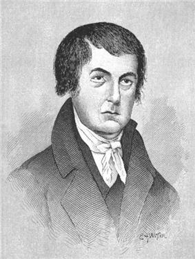 A man with short, black hair wearing a black jacket and vest and white shirt and tie