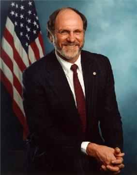 Three-quarter photographic portrait of a white man in his 50s, dressed in a suit and tie. He is balding but has a grayish beard, and he is wearing glasses.