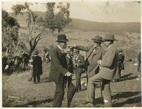 Three middle-aged men with short beards in formal suits and hats standing in open hilly field with single tree nearby