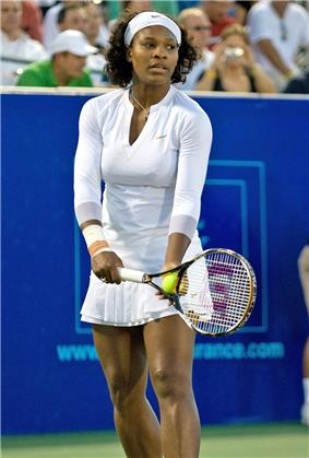 An African American woman in all white clothing, shirt, bandanna, and skirt, is starting the serve of a tennis ball