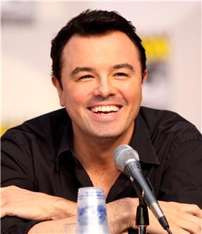 A man with black hair and a black shirt, leaning forward, smiling into a microphone