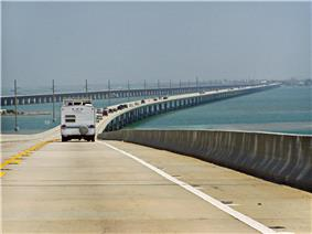 A view of a long bridge over water: a number of cars are visible in the left hand lane