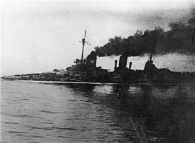 A large gray warship, heavily flooded, its deck is nearly submerged. Thick black smoke pours from the funnels. An in-photo caption reads:
