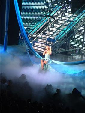 Distant image of a blond woman. She is sitting on a swing hanging from two pieces of fabric. Smoke surrounds her. She is wearing a dress and has her legs crossed. She is holding a microphone and grabbing the swing.