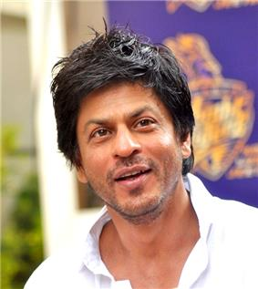 Shah Rukh Khan in a white shirt is interacting with the media