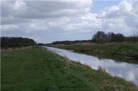 Straight watercourse running between flat grassy fields.