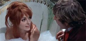 A color screenshot from the film, The Fearless Vampire Killers. Tate is sitting in a large ceramic bathtub, filled with bubbles up to her shoulders. Strands of hair from her red wig are draped over her face, as she looks, smiling, at Roman Polanski, who is leaning towards her at the side of the bathtub.