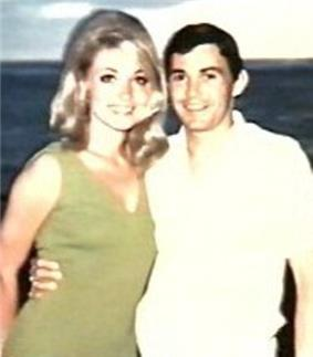 Sharon Tate and Jay Sebring photographed in 1966. They are standing side by side with an ocean background. Tate is wearing a sleeveless dress and Sebring a white shirt. They are standing close together. Sebring has his arm around Tate and they are looking directly into the camera, smiling.