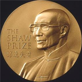 A gold circular medal with a depiction of an elderly man with glasses wearing a jacket buttoned to the neck; the English words