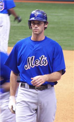 A man in a blue baseball jersey with