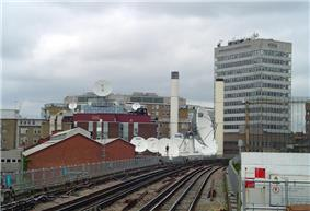 A series of white satellite dishes on the roofs of buildings with a railway track in the foreground all under a light blue sky with white clouds