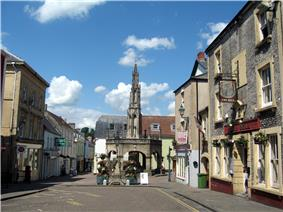 Street scene with buildings on the left and right. In a central position is a stone arched building with a spire.